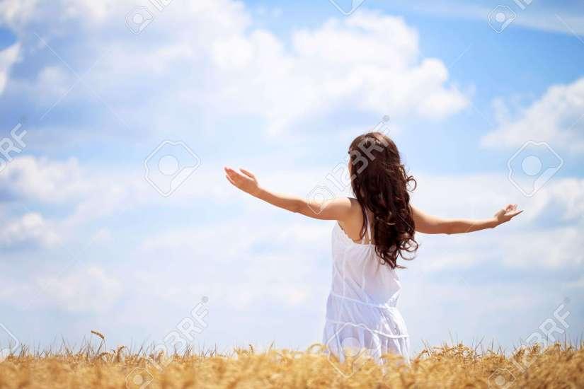 15074981-Mujer-en-campo-de-trigo-disfrutando-concepto-libertad-Foto-de-archivo
