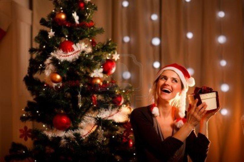 11374653-mujer-interesada-cerca-del-arbol-de-navidad-sacudiendo-caja-presente-tratando-de-adivinar-lo-que-hay